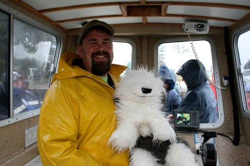 The Captain stays dry inside the cabin today and shows Fluffy the steering and controls of the research boat.